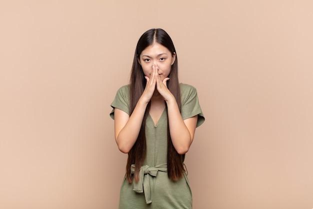 Giovane donna asiatica che si sente preoccupata, piena di speranza e religiosa, prega fedelmente con i palmi premuti, chiedendo perdono
