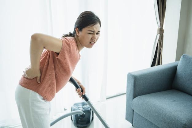 La giovane donna asiatica sente il mal di schiena dopo aver fatto i lavori domestici per un po', la governante ha un problema fisico a causa del duro lavoro. casalinga donna ferita alla schiena a causa di un problema di salute critico.
