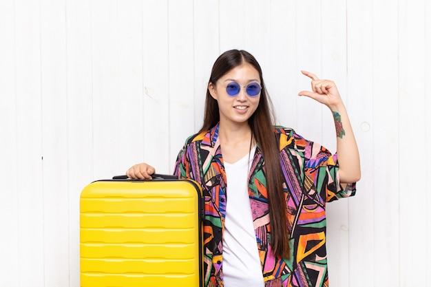 Giovane donna asiatica che incornicia o delinea il proprio sorriso con entrambe le mani, guardando positivo e felice, concetto di benessere. concetto di vacanze