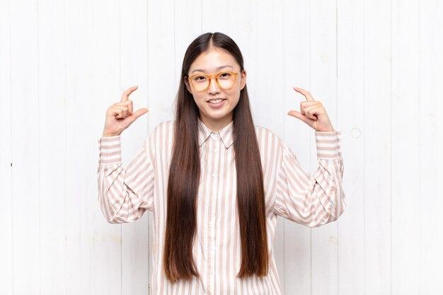 Giovane donna asiatica che incornicia o delinea il proprio sorriso con entrambe le mani, guardando positivo e felice, concetto di benessere
