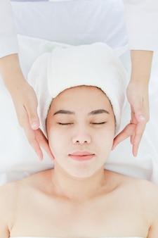 Giovane donna asiatica che ottiene trattamento della stazione termale al salone di bellezza. massaggio viso spa. trattamento di bellezza del viso