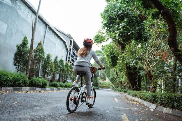 La giovane donna asiatica va indossando un casco per andare in bicicletta pieghevole