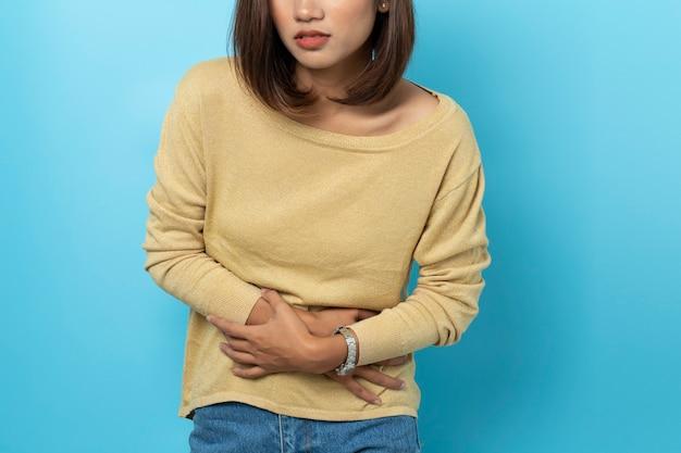 Giovane donna asiatica che ha mal di stomaco doloroso
