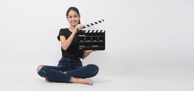 Giovane donna asiatica che tiene bordo di valvola nero o ardesia di film o assicella e si siede sul pavimento. uso nella produzione di video, film, film, industria cinematografica su sfondo bianco.