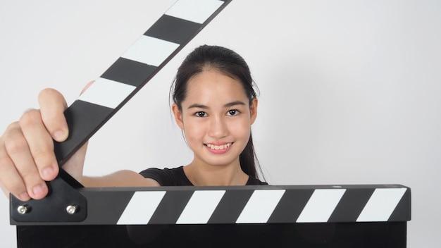Giovane donna asiatica che tiene bordo di valvola nero o ardesia di film o ciak. uso nella produzione di video, film, film, industria cinematografica su sfondo bianco.