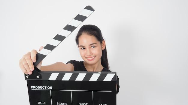 Giovane donna asiatica che tiene ciak nero o ardesia di film uso nella produzione di video, film, industria cinematografica su sfondo bianco.