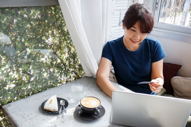 Modello asiatico della carta di credito della tenuta della giovane donna e computer portatile usando