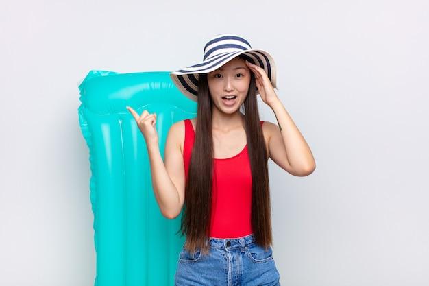 Giovane donna asiatica che ride, che sembra felice, positiva e sorpresa, realizzando una grande idea che punta al laterale