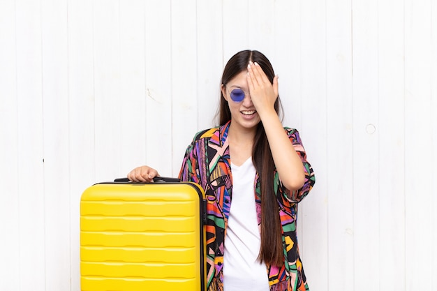 Giovane donna asiatica che ride e che schiaffeggia la fronte isolata