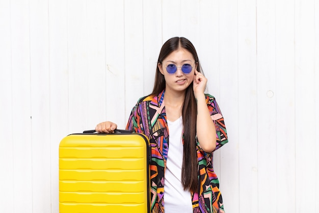Giovane donna asiatica che sembra arrabbiata, stressata e infastidita, coprendo entrambe le orecchie con un rumore assordante, un suono o una musica ad alto volume. concetto di vacanze