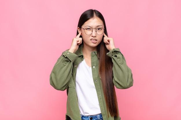 Giovane donna asiatica che sembra arrabbiata, stressata e infastidita, coprendo entrambe le orecchie con un rumore assordante, un suono o una musica ad alto volume