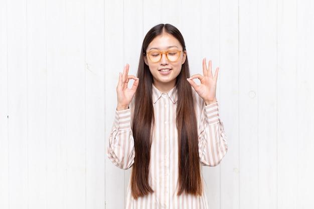 Giovane donna asiatica che sembra concentrata e medita, si sente soddisfatta e rilassata, pensa o fa una scelta