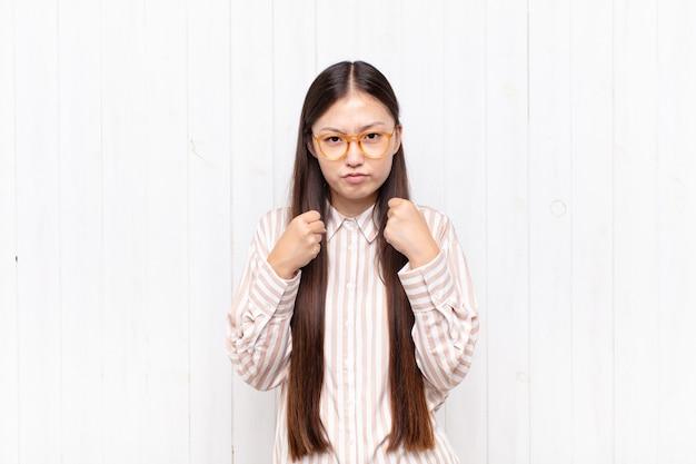 Giovane donna asiatica che sembra sicura, arrabbiata, forte e aggressiva, con i pugni pronti a combattere in posizione di boxe