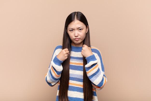Giovane donna asiatica che sembra sicura, arrabbiata, forte e aggressiva