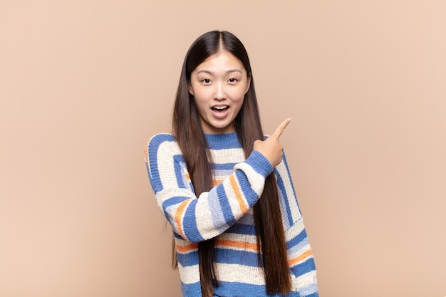 Giovane donna asiatica che sembra eccitata e sorpresa che indica di lato e verso l'alto per copiare lo spazio