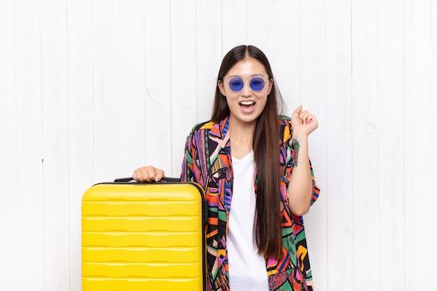 Giovane donna asiatica che sembra estremamente felice e sorpresa, celebrando il successo, gridando e saltando. concetto di vacanze