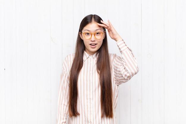 Giovane donna asiatica che sembra felice, stupita e sorpresa, sorridendo e realizzando incredibili e incredibili buone notizie