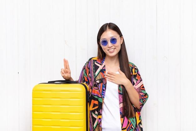 Giovane donna asiatica che sembra felice, sicura e degna di fiducia, sorridente e mostrando il segno di vittoria, con un atteggiamento positivo. concetto di vacanze