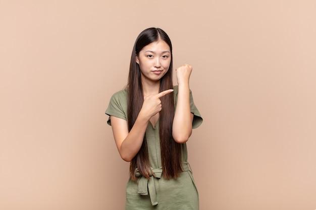 La giovane donna asiatica che sembra impaziente e arrabbiata, indicando l'orologio, chiedendo puntualità, vuole essere puntuale