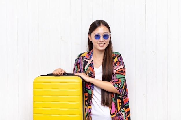 Giovane donna asiatica che sembra un realizzatore felice, orgoglioso e soddisfatto che sorride con le braccia incrociate