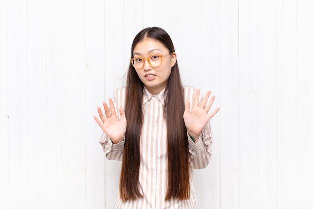 Giovane donna asiatica che sembra nervosa, ansiosa e preoccupata, dicendo che non è colpa mia o che non l'ho fatto