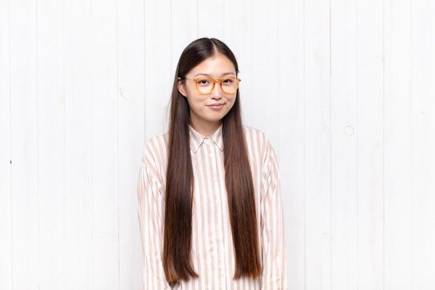 Giovane donna asiatica che sembra orgogliosa, sicura di sé, fredda, sfacciata e arrogante, sorridente, sentendosi di successo