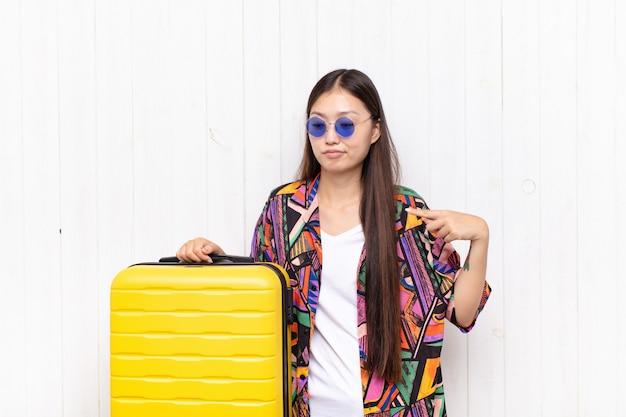 Giovane donna asiatica che sembra che punta orgogliosa, positiva e casuale al petto con entrambe le mani. concetto di vacanze