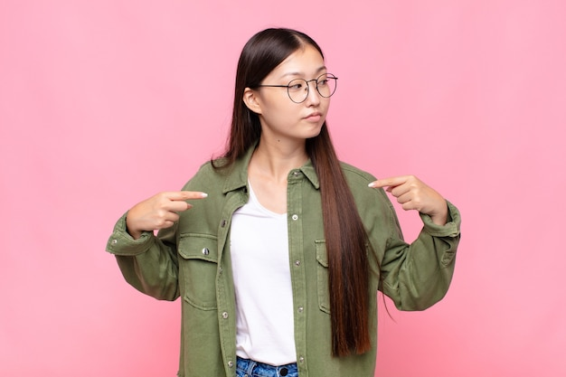 Giovane donna asiatica che sembra che punta orgogliosa, positiva e casuale al petto con entrambe le mani
