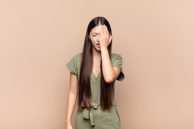 Giovane donna asiatica che sembra assonnata, annoiata e che sbadiglia