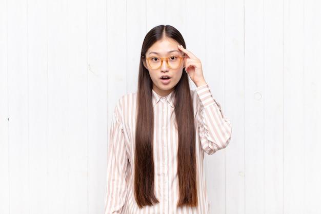 Giovane donna asiatica che sembra sorpresa, isolata a bocca aperta