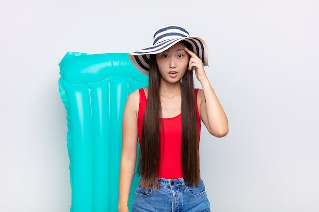 Giovane donna asiatica che sembra sorpresa, a bocca aperta, scioccata, realizzando un nuovo pensiero, idea o concetto. concetto di estate