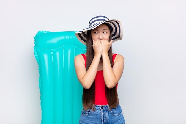 Giovane donna asiatica che sembra preoccupata, ansiosa, stressata e impaurita, mordendosi le unghie e cercando di copiare lo spazio laterale. concetto di estate
