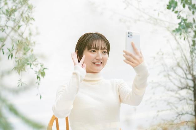 Giovane donna asiatica che fa una chiamata video utilizzando uno smartphone