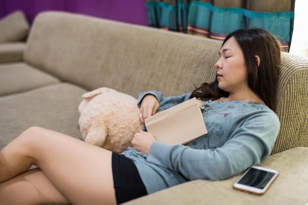 Una giovane donna asiatica fa un pisolino o dorme sul divano dopo aver letto un libro di testo di narrativa in soggiorno. tempo libero e concetto di hobby in casa durante il fine settimana.