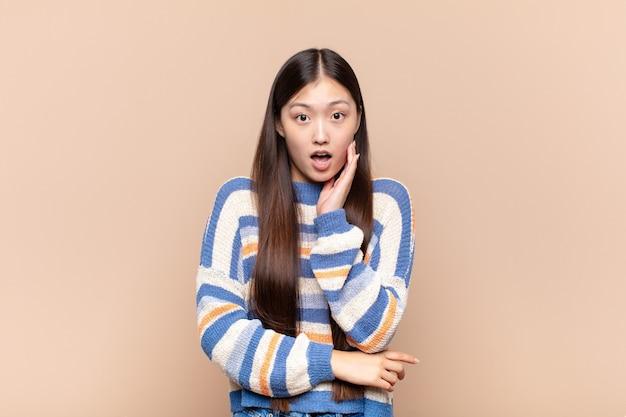 Giovane donna asiatica a bocca aperta per lo shock e l'incredulità, con la mano sulla guancia e il braccio incrociati, sentendosi stupefatta e stupita