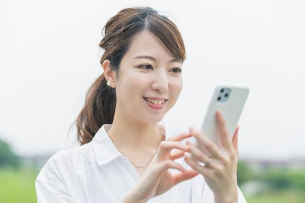 Smartphone operativo della giovane donna asiatica