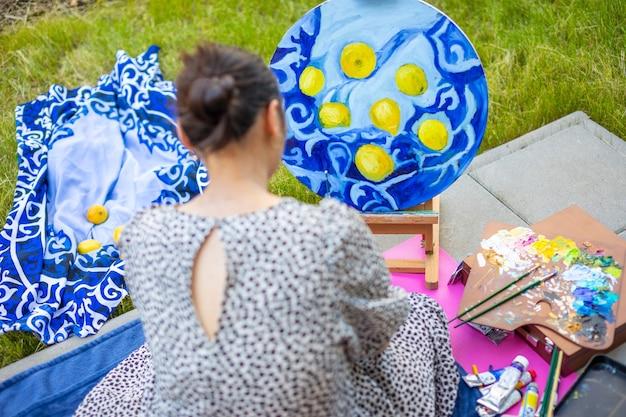 Una giovane donna asiatica che dipinge una foto nella terrazza di casa