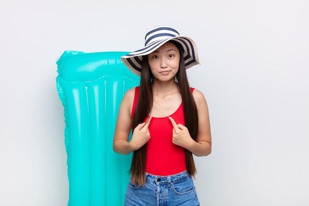 Giovane donna asiatica che indica se stessa con uno sguardo confuso e interrogativo, scioccata e sorpresa di essere stata scelta. concetto di estate