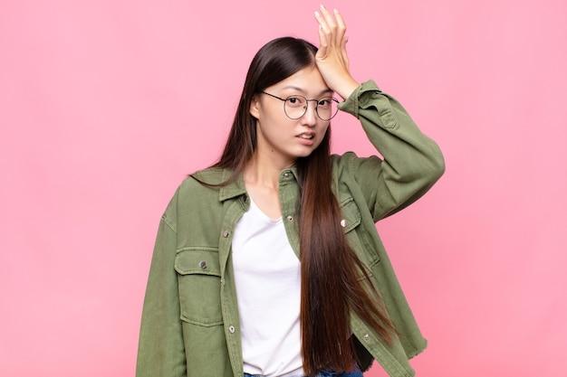Giovane donna asiatica che alza il palmo alla fronte pensando oops, dopo aver commesso uno stupido errore o ricordando, sentendosi stupido