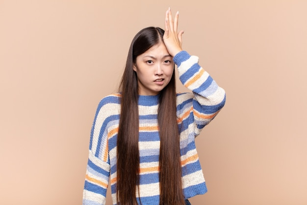 Giovane donna asiatica che alza il palmo sulla fronte