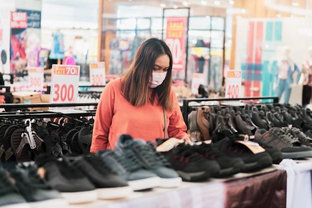 Acquisto asiatico della giovane donna nel centro del centro commerciale con la maschera di protezione medica
