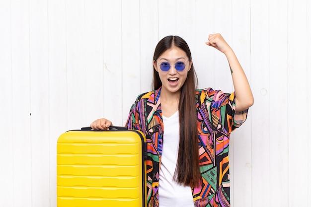 Giovane donna asiatica che grida trionfante, guardando come vincitore eccitato, felice e sorpreso, celebrando. concetto di vacanze