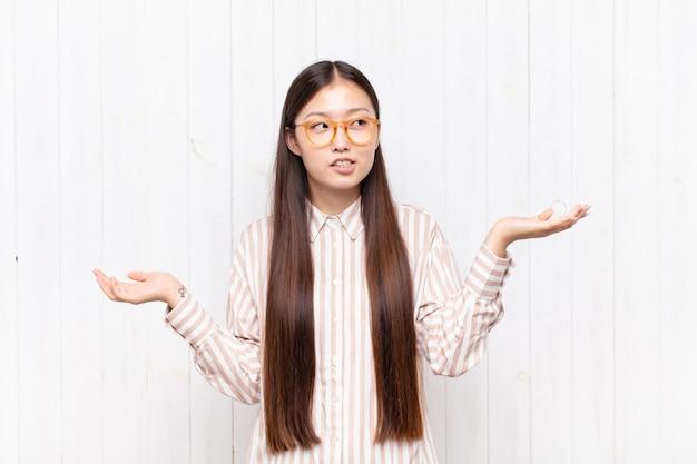 Giovane donna asiatica che scrolla le spalle con un muto, pazzo, confuso