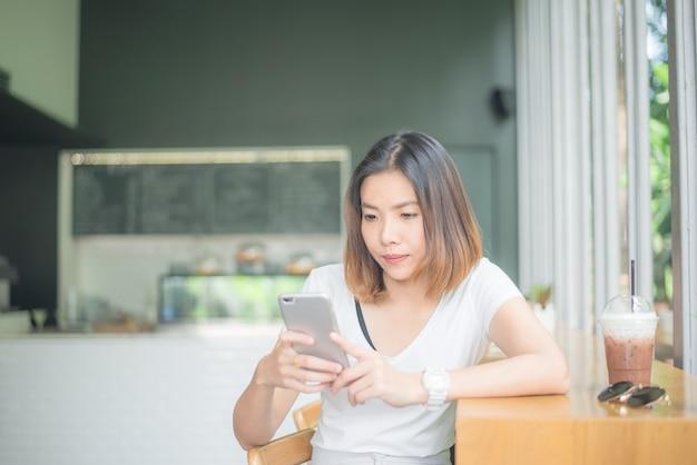 Giovane donna asiatica che si siede vicino alla finestra nel caffè.