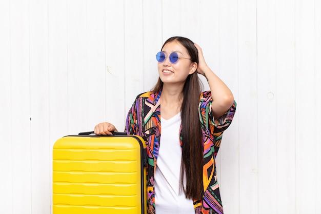 Giovane donna asiatica che sorride allegramente e casualmente, prendendo corpo a corpo con uno sguardo positivo, felice e fiducioso. concetto di vacanze