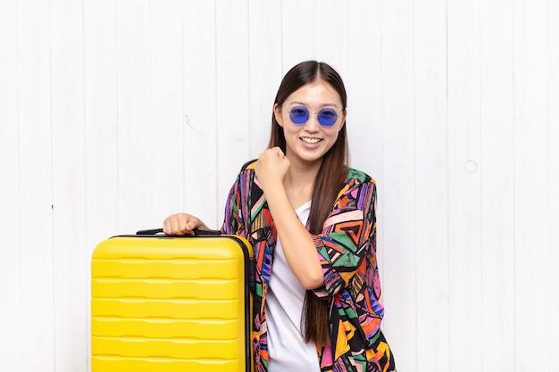Giovane donna asiatica che sorride allegramente e che celebra