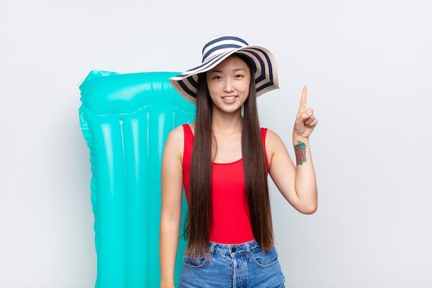 Giovane donna asiatica che sorride allegramente e felicemente, rivolto verso l'alto con una mano per copiare lo spazio. concetto di estate