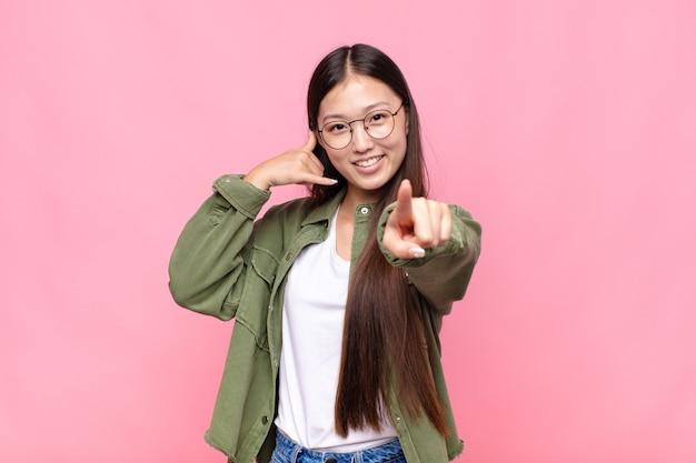 Giovane donna asiatica sorridendo allegramente e indicando la telecamera mentre si effettua una chiamata successiva gesto, parlando al telefono