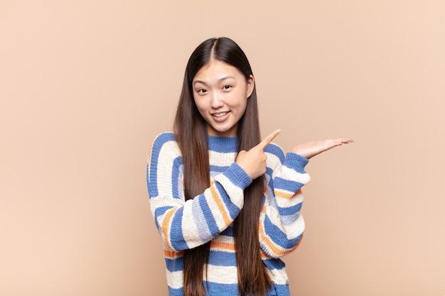 Giovane donna asiatica che sorride allegramente e indica lo spazio della copia sul palmo sul lato, mostrando o pubblicizzando un oggetto