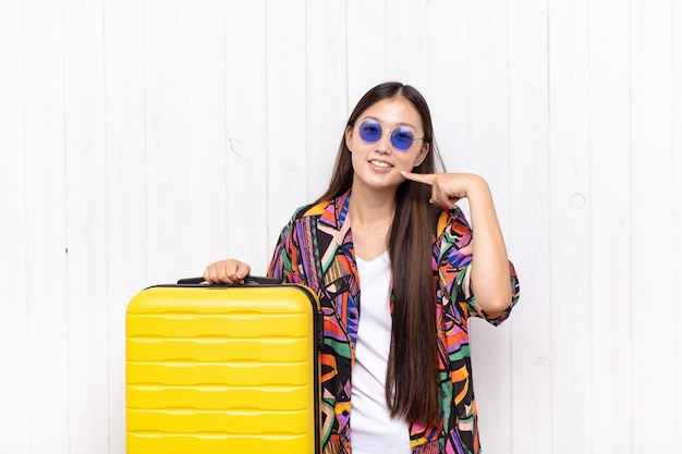 Giovane donna asiatica che sorride fiduciosamente indicando il proprio ampio sorriso